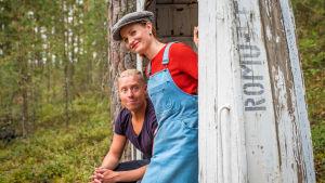 Egenlands programledare Hannamari Hoikkala och Nicke Aldén på ön Hytermä i Kerimäki - brevid en bänk som är gjord av en båt som lyfts upp. På båten står det: Romu-Heikki.