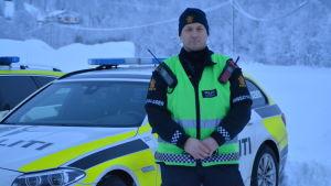 Polis i Tamokdalen framför en polisbil.