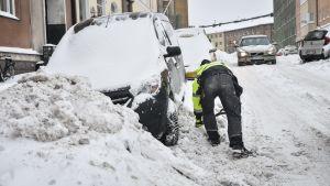 En man skottar snö för att komma loss med bilen i berghäll i Helsingfors tisdagen den 29.1.