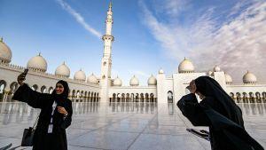 """Muslimska kvinnor tar """"selfies"""" framför moskén i Abu Dhabi inför påvens besök."""