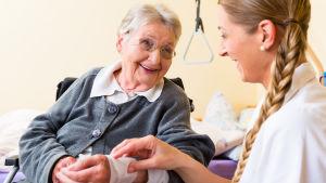 Äldre kvinna får ett bandage runt handleden av en yngre vårdare.