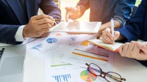 Dokument med grafer och siffror samt glasögon på ett bord. Tre personer sitter runt bordet och tittar på en pekplatta och antecknar.