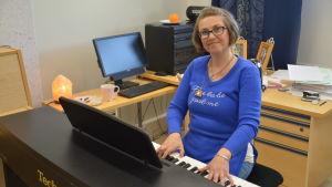 En leende kvinna sitter vid ett piano och tittar in i kameran.