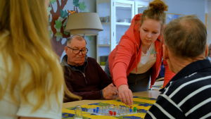 Tove flyttar en röd kimble knapp, en äldre man vid bordet ser på.