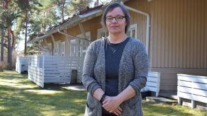 Petra Henriksson står utanför solglimten, vårsolen skiner och gräsmattan är ganska grön.