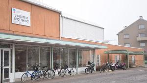 En röd och vit byggnad med cyklar utanför. Hangö idrottshus.