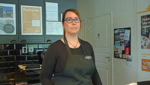 En kvinnlig caféförsäljare bakom disken.