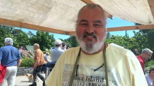 mikael smeds står under ett tygtak och runtom honom passerar festivalbesökare förbi. Han ler mot kameran.