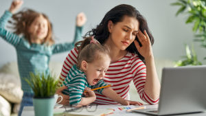 Nainen on stressaantunut lasten kiljuessa ympärillä.