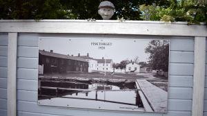 Ett staket med ett gammalt, uppförstorat fotografi och en docka som kikar över staketet.
