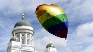 En regnbågsballong formad som ett hjärta vajar i luften.