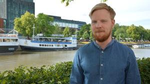Atte Lindqvist tittar in i kameran, i bakgrunden åstranden i Åbo