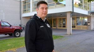 En man i svart munkjacka står framför en dörren till en idrottshall.