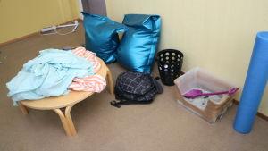 En kattlåda med bajskorv, en väska, två dynor och några lakan på ett bord.