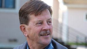 En man med kort mörkt hår och mustasch ler.