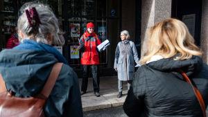 Två kvinnor talar till en grupp lyssnare.