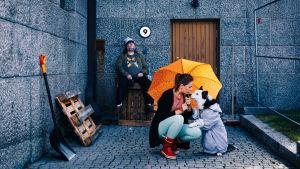 Nainen ja koira ovat oranssisen sateenvarjon alla. Partainen mies istuu taustalla seinän vieressä.