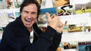 En brett leende Petter Stordalen, i svart tröja, står framför en vägg med färggranna vykort och gestikulerar med händerna.