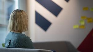 En kvinna tittar på en tavla med post-it-lappar.