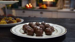 Ett serveringsfat med hemlagade chokladdoppade praliner garnerade med flingsalt.