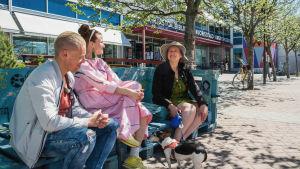Mies ja kaksi naista istuvat kuormalavoista tehdyllä penkillä ja hymyilevät. Heisän vieressään on pieni koira ja taustalla kirjasto sekä puita.