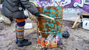 Graffitimålad rostig tunna.