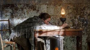 Helene Schjerbeck lutar sig över ett bord i skenet av en oljelampa.