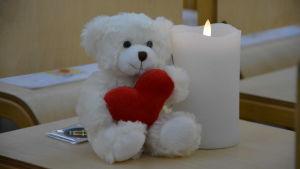 En vit nallebjörn med ett hjärta i famnen sitter intill ett ljus.
