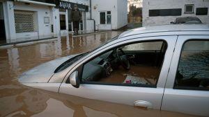 Bil som svämmats över av brunt vatten.