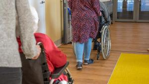 Toiminnanohjaajat työntävät vanhuksia pyörätuolissa Myyrmäen vanhustenkeskuksessa.