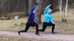 Två kvinnor som stretchar ute i naturen.