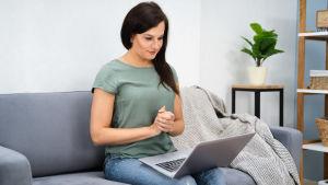 Kvinna som sitter i en soffan med en laptop i famnen.