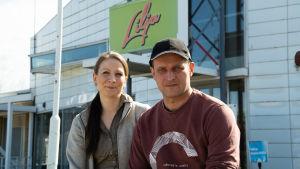 Jenny och Petri sitter utanför servicestationen och tittar in i kameran.