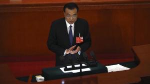 Kinas premiärminister Li Keqiang talar framför folkkongressen. Han står vid ett podium och klappar sina händer.