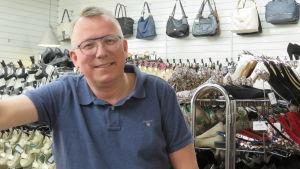 En man med kort hår, glasögon och blå kortärmad pikeskjorta inne i en sko- och väskbutik.
