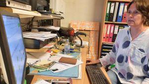 en dam sitter med sin dator vid ett skrivbord fyllt av papper