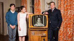 Tv-kuuluttaja Marie Gillain näkyy mustavalkoisessa tv-kuvassa. Tv:n ympärillä poseeraa kuuluttajan perhe: poika Jean-Claude, tytär Colette ja aviomies Pierre