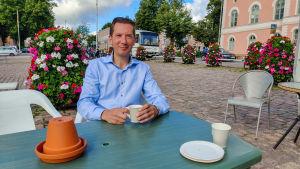 En man i blå skjorta sitter och dricker kaffe vid ett bord på ett torg.