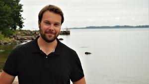 Tomi Ståhlberg har en svart pikéskjorta på sig, har kort skägg och brunt hår. Han ser in i kameran och ser bestämt glad ut. I bakgrunden skymtar Helsingfors och skärgården, och vatten.