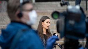 Sanna Marin ger intervjuer på Ständerhusets trappor. I förgrunden ses en kameraman som har på sig ett munskydd.