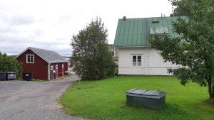 Ett småhus på Åliden i Ingå kyrkby me en röd bod längs ån.
