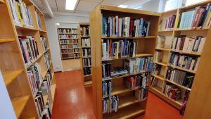 Böcker i trähyllor i ett litet rum med rött golv.
