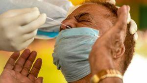 En indisk man testas för coronaviruset.