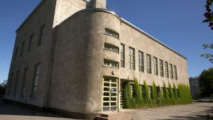 Grå byggnad med både runda och raka former och många fönster.