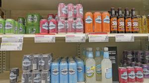 Butikshylla i Alko där man kan se bland annat burkar av lonkero.