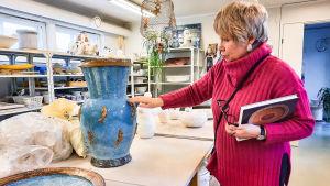 En kvinna i pink tröja står intill ett bord med keramikgföremål på. Hon sträcker ut handen och rör vid en blå kruka. I famnen håller hon en bok och sina glasögon.