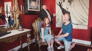Kolme henkilöä taidegalleriassa, nainen istuu tuolilla, mies polviseisonnassa lattialla, taustalla hymyilee gallerian omistaja