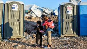 Barn som väntar utanför kemiska toaletter i flyktinglägret Kara Tepe