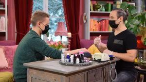 Nicke Aldén och Alexey Kriventsov sitter mittemot varandra vid en gammal byrå. Båda har på sig svarta munskydd och manikyren ska strax inledas.