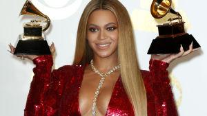 Artisten Beyoncé iklädd röd klänning håller upp två Grammy-pris.